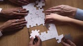 assembler : Above close up view hands multi-ethnic business people teammates connects together white pieces of jigsaw puzzle on office desk, participating team building activity, search solutions, synergy concept Vidéos Libres De Droits
