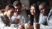 travessura : Different ethnicity colleagues spend free time lunch together gathered in cafe drink coffee laughing feels overjoyed, girl showing to friends funny video hold cellphone having fun online prank concept Vídeos