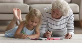 emocje : Old senior grandma baby sitter help teach cute little kid granddaughter drawing with felt pen together, mature retired grandmother nanny and grandchild girl playing creative activity on floor at home