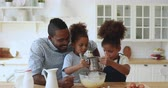 backen : Cute african american family young father dad with mixed race little children kids siblings preparing dough together whisking flour and eggs having fun cooking baking cake cookies in modern kitchen Videos
