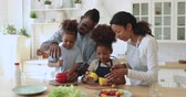 mama : Happy african family mom dad and small cute kids cut fresh vegetable salad cooking together in modern kitchen, mixed race parents teach little children son daughter help prepare healthy food at home