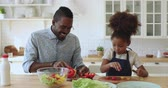 emocje : Happy family african dad and funny small kid daughter cooking together, young father teach cute mixed race child girl learn cut fresh healthy vegetable salad talking laughing having fun in kitchen