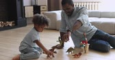 отопление : Happy african american family young dad babysitter and cute small kid son pretending dinosaurs battle sit on floor at home, father playing game with little child boy holding toys having fun together