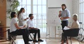 antreman : Confident businessman male company ceo coach mentor trainer speaking teaching multiethnic staff people presenting new corporate strategy on whiteboard flip chart at corporate office workshop training. Stok Video
