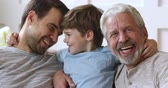 zoon : Cheerful intergenerational 3 three generation men family closeup portrait, happy little boy son grandson cute face embrace young father and old grandpa look at camera laugh hug bond together at home Stockvideo