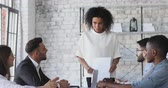 etnický : Young mixed race female company leader discuss paperwork report at team meeting, african businesswoman executive review work results brainstorm with employees group at corporate briefing table Dostupné videozáznamy