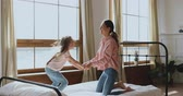 anyaság : Happy active cute small kid girl jumping on bed playing with young adult mother having fun in modern bedroom interior, carefree kid daughter and her parent mum enjoying leisure morning games at home