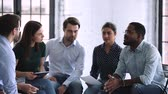 indianin : Friendly creative multiethnic marketing team people brainstorming share ideas talking working together in teamwork discuss new project plan sit on chairs in circle office at group corporate meeting
