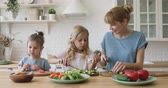kleine kinder : Happy little girl eating vegetables while eldest sister preparing salad with caring mommy at kitchen. Cheerful pleasant young babysitter nanny talking to small sisters, teaching cooking food.