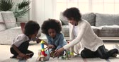 školka : Happy young adult african parent mom babysitter playing wooden blocks and dinosaurs toys with cute kids small son and daughter sit on warm floor carpet enjoy weekend activity in living room at home Dostupné videozáznamy