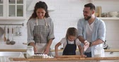 školka : Overjoyed married couple playing with flour while little preschool daughter learning using rolling pin in modern kitchen. Happy full family having fun, preparing homemade bakery together at home.