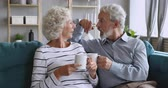 Affectionate mature family couple relaxing on cozy sofa, enjoying pleasant conversation, holding cups of hot tea. Loving happy middle aged man joking talking discussing with elderly smiling wife. Stock Footage