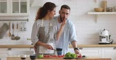 Young handsome man cuddling from back smiling attractive wife in apron preparing healthy vegetarian dish for romantic dinner. Joyful millennial woman feeding loving husband while cooking in kitchen.