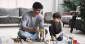 blokken : Happy young adult parent dad and child son play toys sit on floor carpet at home, caring father having fun help cute kid build tower of wooden blocks enjoy game activity give high five in living room