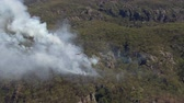 назад : A wide shot of smoke and trees and mountain. Camera moves backward