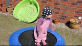 Little girl (one year and five months old) is trying to jump on the trampoline