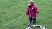 Little girl (one year and 6 months old) watering grass lawn in the yard with a hose