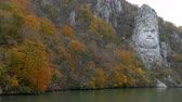 kings canyon : Autumn at the Danube Gorges, the border between Romania and Serbia. View with the Decebal Kings Head sculpted in rock and inscription DECEBAL REX - DRAGAN FECIT (Decebal King - Made by Dragan). Stock Footage