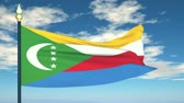 comoros : Flag Of Comoros on the background of the sky and flying clouds.