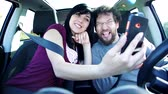 men : Happy couple in car taking selfie picture with cell phone while driving Stock Footage