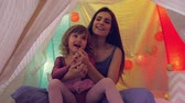 kids tent : Beautiful woman with daughter playing in slow motion colorful tent Stock Footage