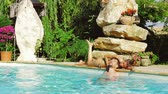 Boyfriend and girlfriend enjoying peace in swimming pool of hotel in Italy