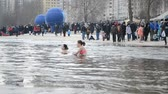 крещение : Epiphany near Svjato-Pokrovskiy Cathedral on January 19,2014 in Kiev,Ukraine.People plunging into ice-cold water as it helps body became resilient to illness. Epiphany known since 988 AD. Стоковые видеозаписи