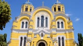 batismo : KIEV, UKRAINE - JUN 08: St. Vladimir Cathedral aka Volodymyrsky Cathedral yellow stone building with blue sky and green park trees on June 08, 2018 in Kiev, Ukraine. It is place for Christian wedding, Easter and Sunday holiday ceremony for all christian p Vídeos