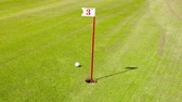 golfing : hole on the Golf course with a number. Playing Golf on the green grass. and the player picking up the Golf ball. UHD video