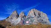 passo : Signboard Val Gardena, Groeden with costume couple at Sella Pass, Alto Adige. South Tyrol, Italy, Europe Stock Footage