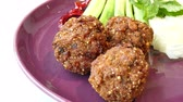 quibe : Spicy marinated pork balls served with vegetable
