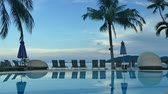 вилла : Swimming pool with umbrella and chair on sea view background Стоковые видеозаписи