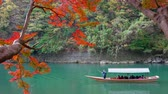 KYOTO, JAPAN - NOVEMBER 15, 2018 : Boatman punting the boat at river. Arashiyama in autumn season