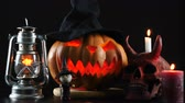temető : Halloween. Pumpkin, skull, oil lamp, candle, witch standing on table.