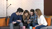 cosiness : Multinational company sit on the couch and discuss funny video seen on the tablet 50 fps Stock Footage
