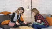 piada : Asian and Caucasian girls playing backgammon 50 fps