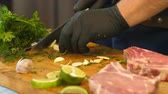 dill : Mens hands in black gloves cut garlic into small pieces