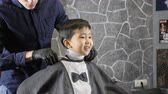 hair cut : Barber covering the Asian child with a cloak, the child laughing 60 fps Stock Footage