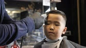 nape : Barber in black gloves gently shaves bangs Asian child 60 fps Stock Footage