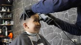 nape : Barber in black gloves gently shaves bangs happy Asian child 60 fps Stock Footage