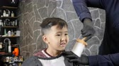 nape : Barber in black gloves removes hair from the neck of an Asian child 60 fps