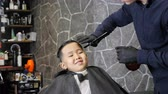 nape : Barber in black gloves spraying and combing on the hair of an Asian kid 60 fps Stock Footage