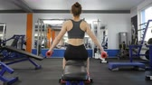 dumbell : Sports young girl doing side dumbbell raises while sitting on sports bench in a gym. Back side view 60 fps Stock Footage