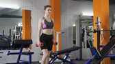 lunges : Young beautiful sporty girl doing lunge with dumbbells in gym. 60 fps