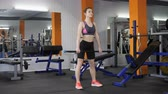 practising : Young beautiful sporty girl performs Romanian deadlift with a barbell in a gym, front side view 60 fps