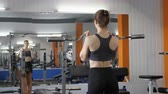 kas inşa : Young beautiful sporty girl lifting barbell bar in gym, pumping biceps. 60 fps Stok Video