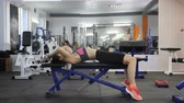 kas inşa : Sports young girl doing triceps exercise with bar while lying on the sports bench in a sport gym. Side view 60 fps
