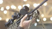 nato : A sniper rifle in the hands of a man, an optical sight, a backdrop, a bokeh 60 fps