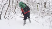 bengala : Old caucasian man makes his way with Hiking Sticks through thickets in a dense snowy forest. Thick dense thicket of trees and roots in in the snow-covered forest. Hike and travel concept, snow is falling back side view 60 fps Vídeos