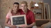 severler : A sad international gay couple is sitting on the couch and holding a sign. We are not afraid. Look at the camera. Home comfort on the background. 60 fps Stok Video